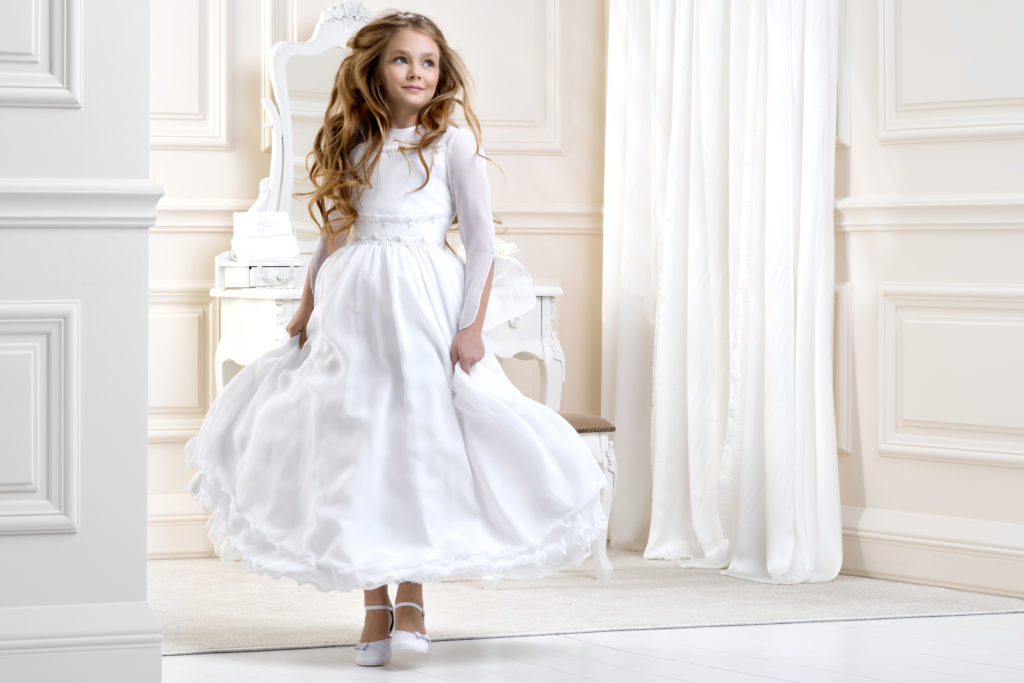 Stunning beauty young girl model in the white communion dress stands in an elegant palace